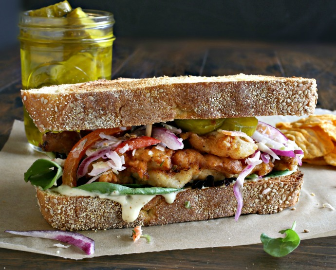 Recipe for chicken, marinated in buttermilk, coated, fried and served on toasted bread.