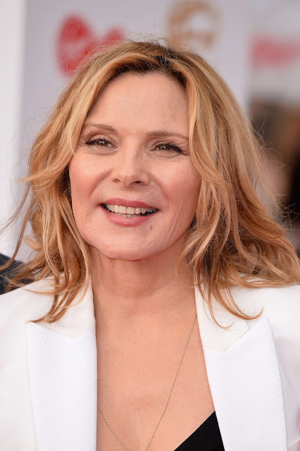 Actress Kim Cattrall Shows Off Her Cleavage in Black Dress and White Jacket Actress Trend