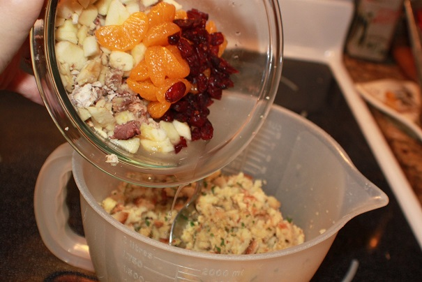 this is the ingredients to make a chestnut stuffing in a tupperware bowl and in a glass bowl pouring them into each other. There is stuffing, craisins, mandarin oranges and chestnuts