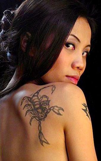modelo asiatica, de espldas se gira mirandonos sensualmente, lleva en el omoplato un tatuaje de escorpion