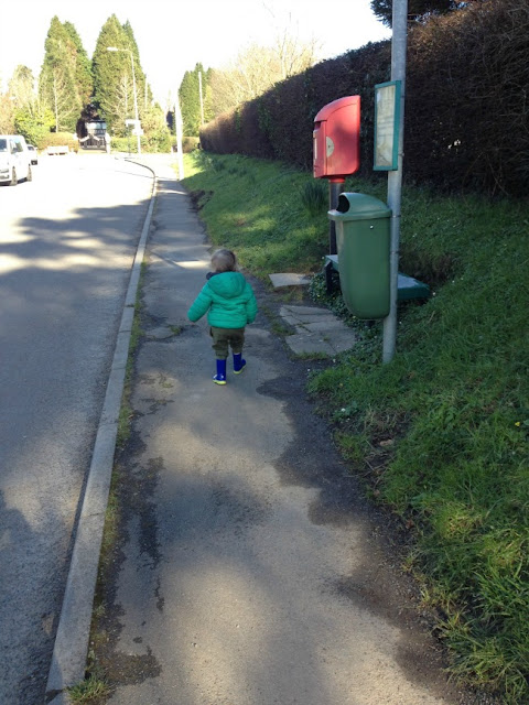 Back of a toddler walking on path next to a quiet road in sunshine