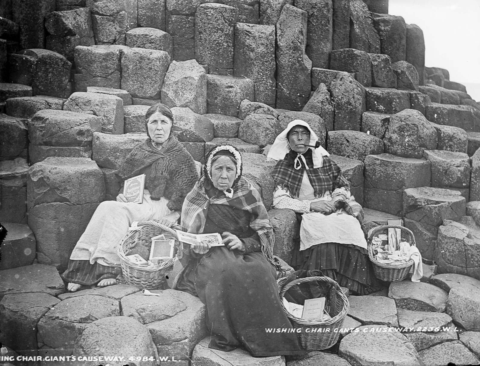 Women sell tourist trinkets and books on Fionn Mac Cumhaill's Wishing Chair at the Giant's Causeway, County Antrim. 1900.
