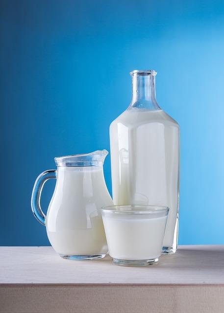 Botella de Vidrio con Liquido color blanco en un Fondo color Azul