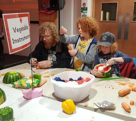 2 boys and father making instruments from vegetables and all engrossed in their carving