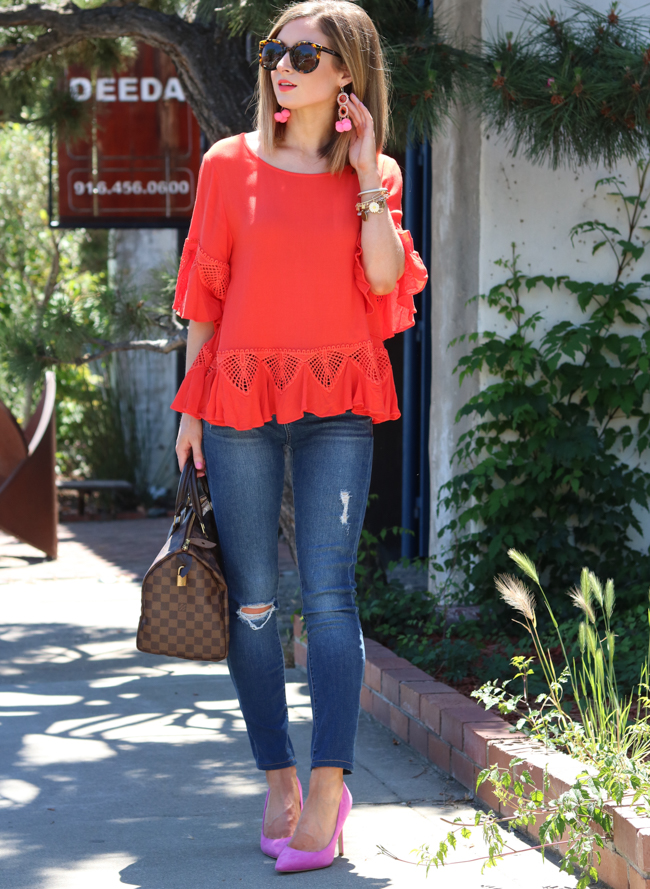 Orange top with pink pom earrings.