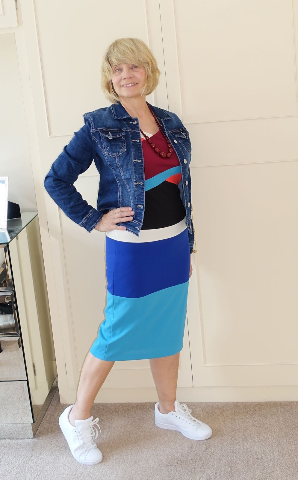 A denim jacket and white trainers give a more casual look to an asymmetric colour blocked dress