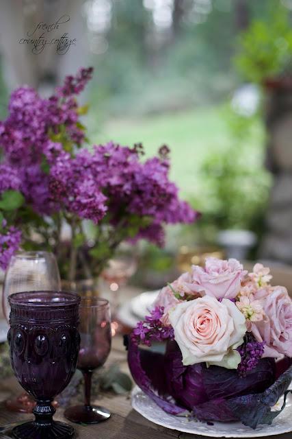 cabbage vase with lilacs and roses on table