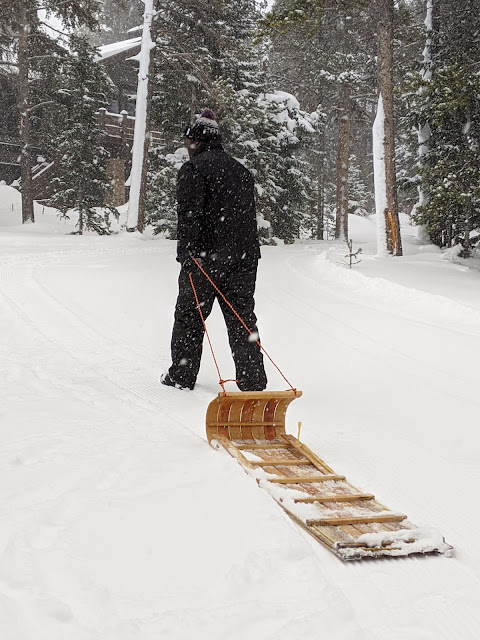 young black man pulling toboggan sled in the snow for winter vacation