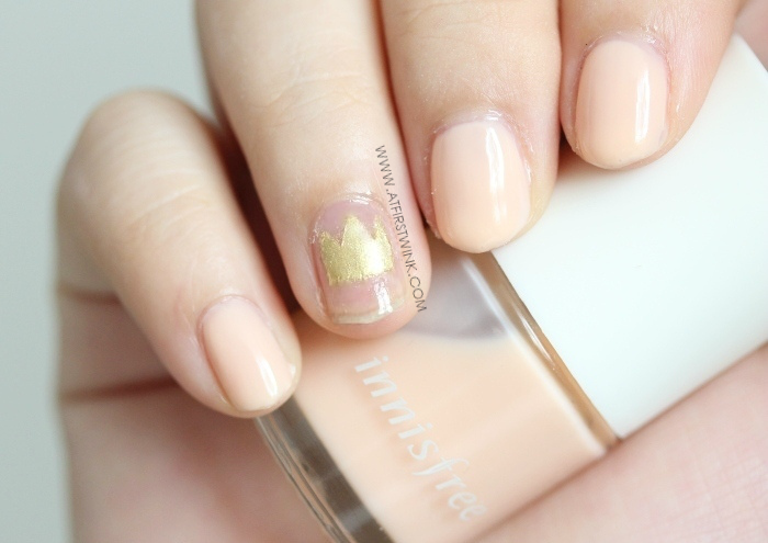 gold crown nail art and pale orange nail polish (Innisfree)