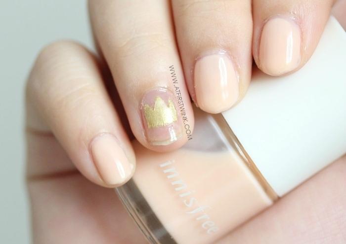 gold crown nail art and pale orange nail polish (Innisfree)