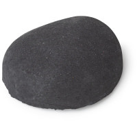 A dark grey oval shaped shower bomb with a silvery grey underside on a bright background