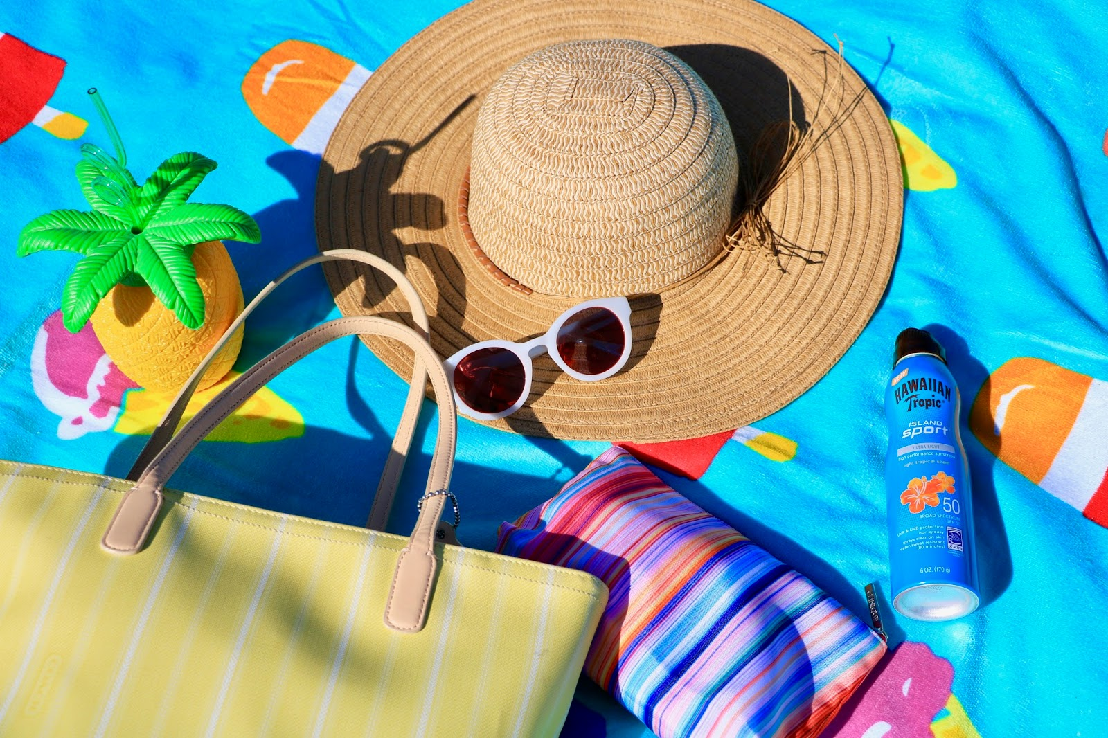 Beach towel blanket with hat, sunglasses, and sunscreen