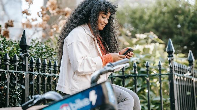 Mulher sentada ao ar livre olhando o celular. Ela usa casaco, tem cabelo longo e cacheado, está do lado de uma bicicleta desfocada.