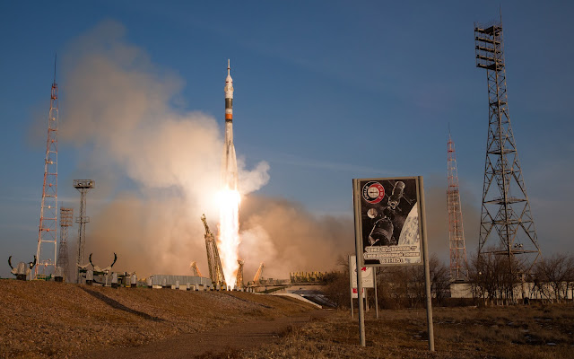 With a sign commemorating the 1975 Apollo-Soyuz mission in the foreground, the Soyuz TMA-19M spacecraft launched from the Baikonur Cosmodrome in Kazakhstan, Tuesday, Dec. 15, 2015, sending Expedition 46 Flight Engineer Tim Kopra of NASA, Soyuz Commander Yuri Malenchenko of the Russian Federal Space Agency (Roscosmos) and Flight Engineer Tim Peake of ESA (European Space Agency) to orbit for the start of six-month mission on the International Space Station. Photo Credit: (NASA/Joel Kowsky)