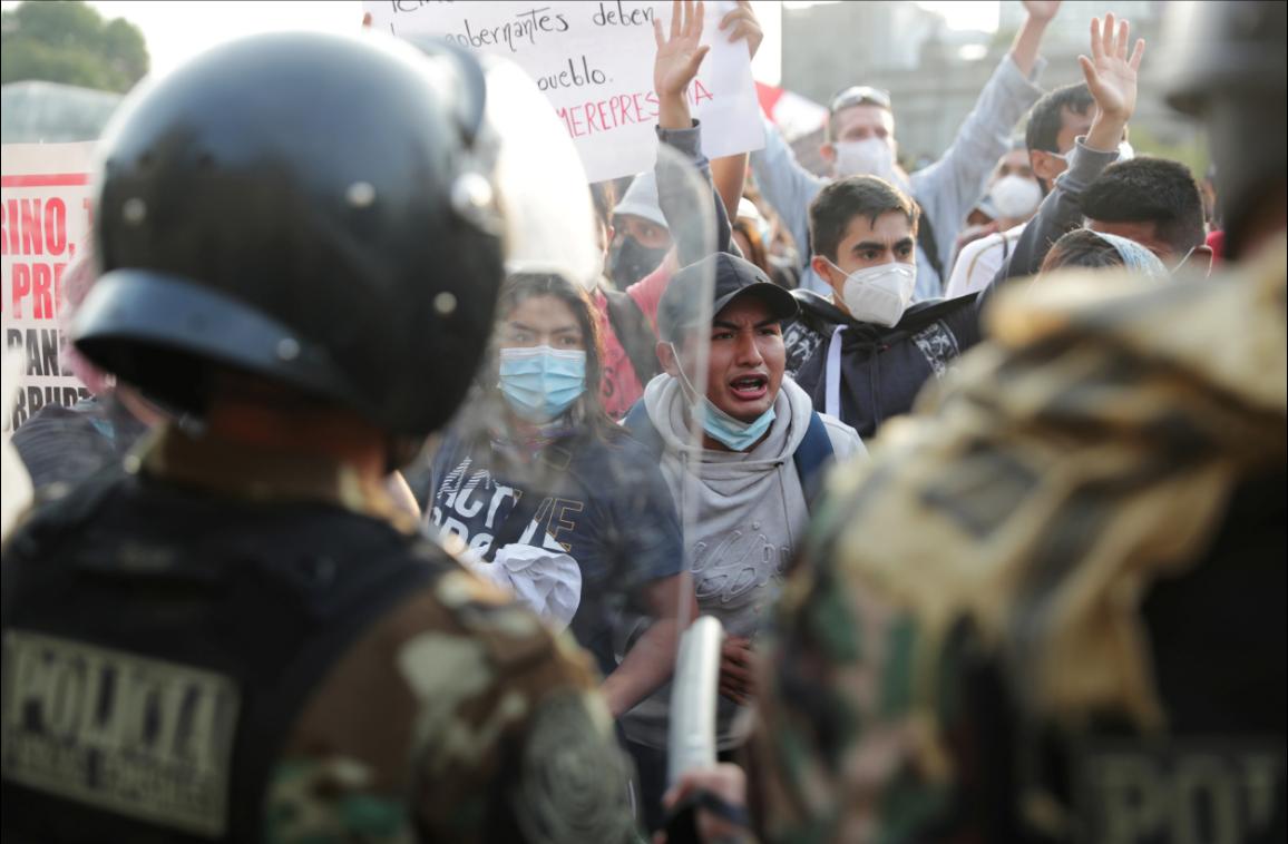 Agentes de policía bloquean a manifestantes durante las protestas tras el juicio político al presidente Martín Vizcarra, en Lima, el 11 de noviembre de 2020 / VOA