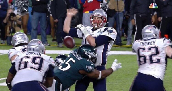 image from game of Brady as the ball gets knocked out of his hand before he can throw it