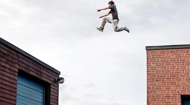Adolescente em atividade perigosa saltando prédio, psicologia do comportamento de risco