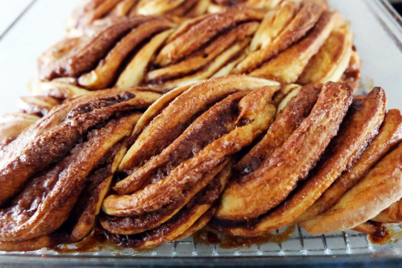 close up of twisty cinnamon rolls in pan