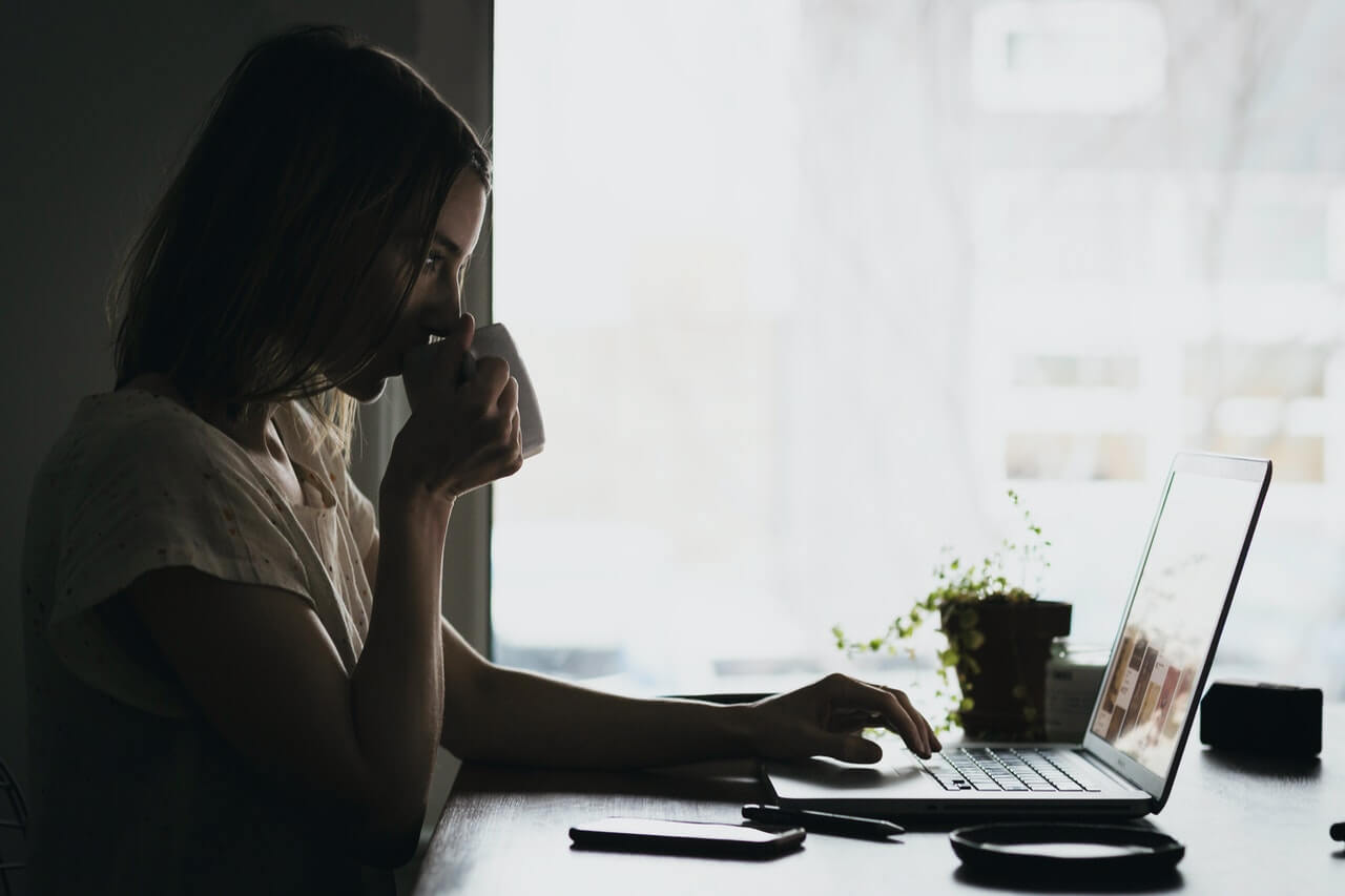 Woman at Computer Desk Drinking Coffee