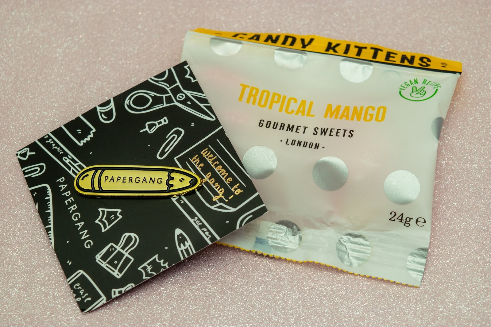 A pin on black card. The pin is gold in the shape of a pencil with the word Papergang on it. The sweets are tropical mango Candy Kittens.