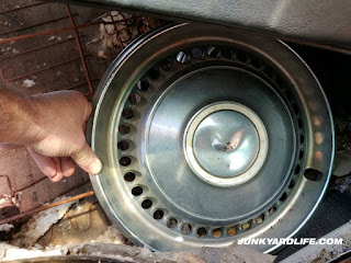 Complete set of 14-inch hub caps found inside Chevy Nova.