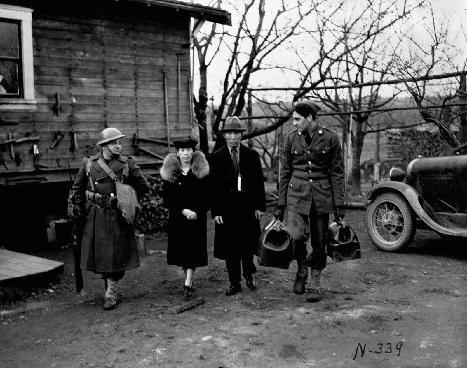 Los soldados escoltan a una pareja de ancianos japoneses-estadounidenses desde su hogar en la isla de Bainbridge, Washington.