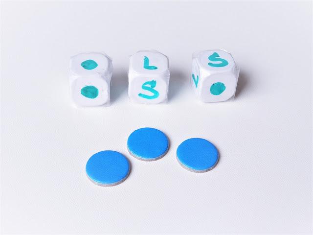 na obrazku widać trzy kostki do gry, pierwotnie czyste, teraz obklejone taśmą klejącą i opisane symbolami P, L, Ś oraz kropką, przed kostkami leża trzy żetony w kolorze niebieskim, wszystko to elementy gry lewy, prawy, środek