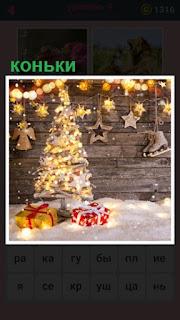 на стене висят коньки и стоит горящая ёлка с подарками