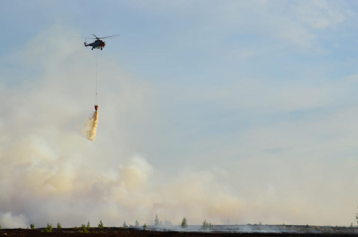 Helikopters nomet ūdeni ugunsgrēka vietā