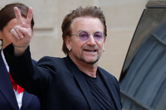 A imagem mostra o cantor Bono Vox acenando para a câmera. Ele é caucasiano, usa terno preto e um óculos roxo. Ele está sorrindo.