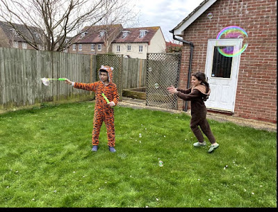 Children playing with bubbles in the garden