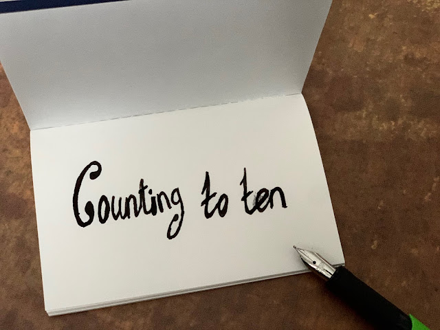 Counting to ten written next to a fountain pen