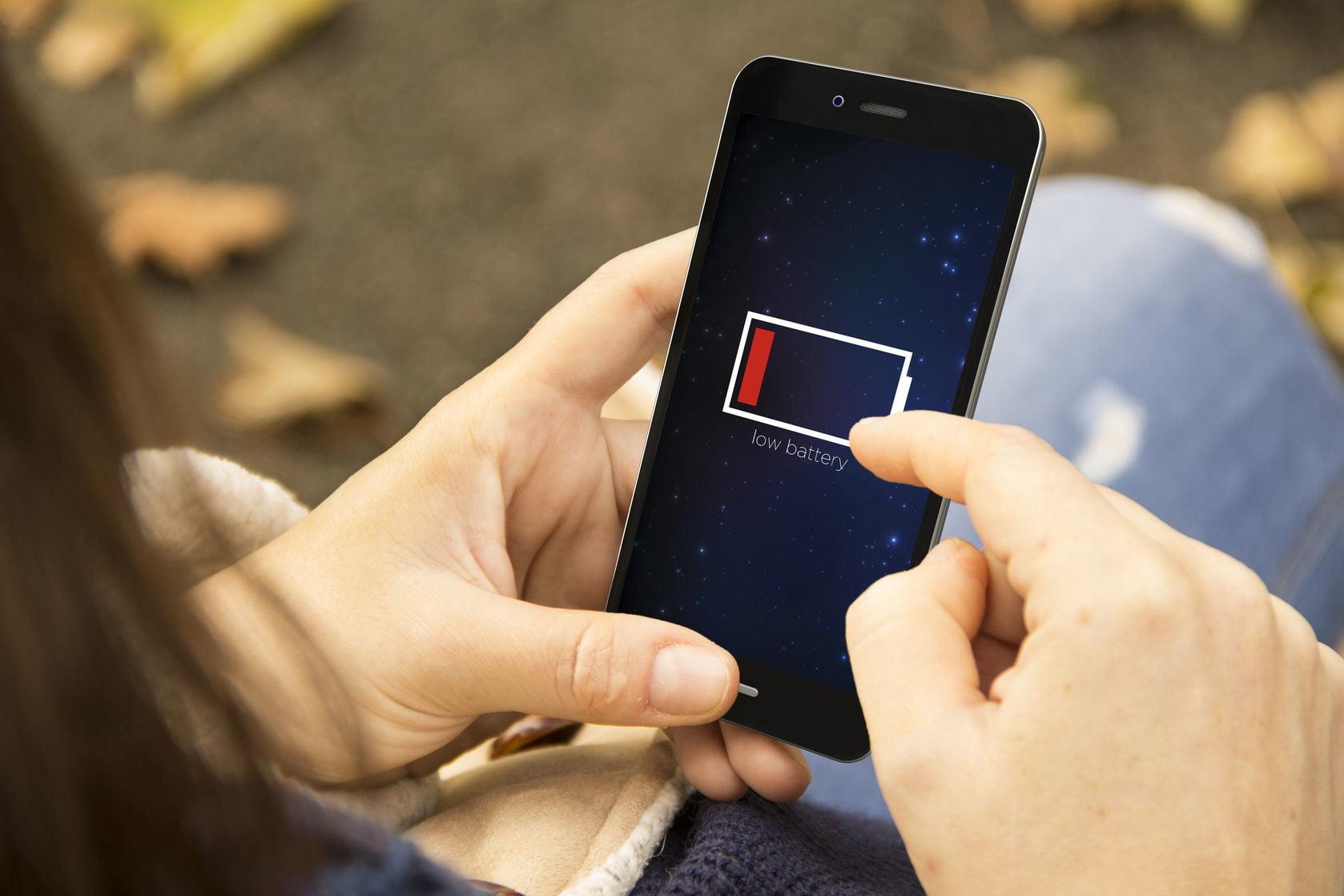 celular com bateria descarregada na mao de uma mulher