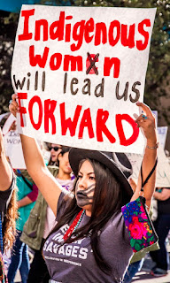 """A woman with long dark hair and a black hat holding up a white sign with red lettering. It says """"Idigenous women will lead us forward"""" . Taken at the International Woman's Day 2019 March in Tucson, AZ. Photo by Dulcey Lima on Unsplash."""