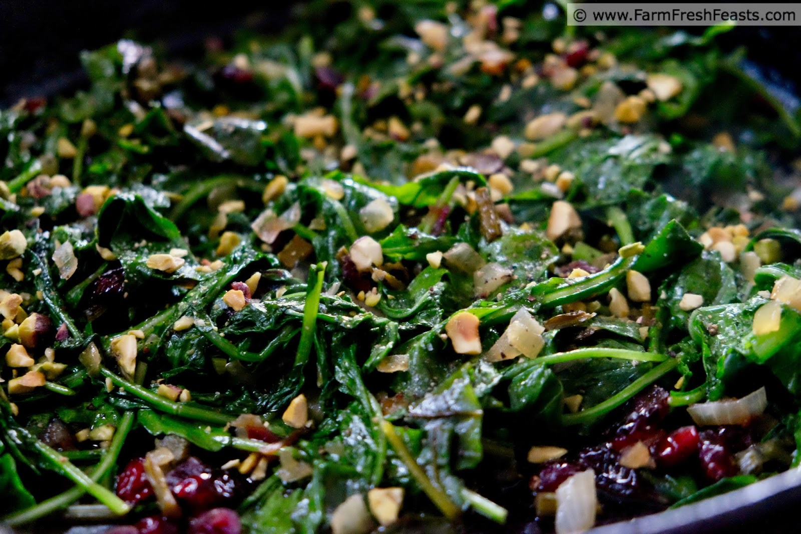 close up of a skillet of sautéed mixed greens with cranberry and pistachio