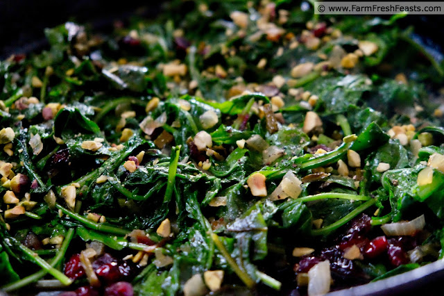 close up image of a skillet filled with sautéed mixed greens topped with cranberry and pistachio