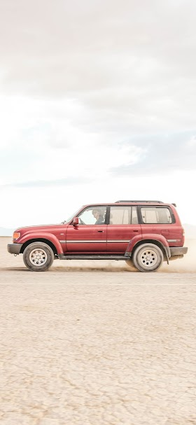 خلفية سيارة حمراء تسير في الصحراء