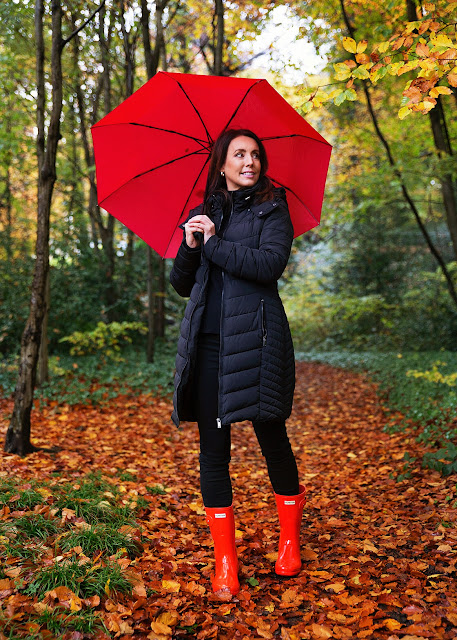 Woman wearing red hunter boots in autumn leaves