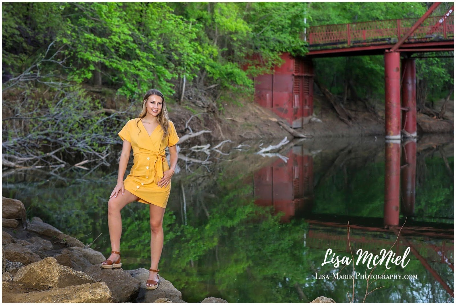 teen girl in yellow dress by river and bridge