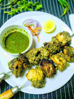 Serving hariyali kabab with shewer in a plate green chutney, onion slices, lemon wedges in background