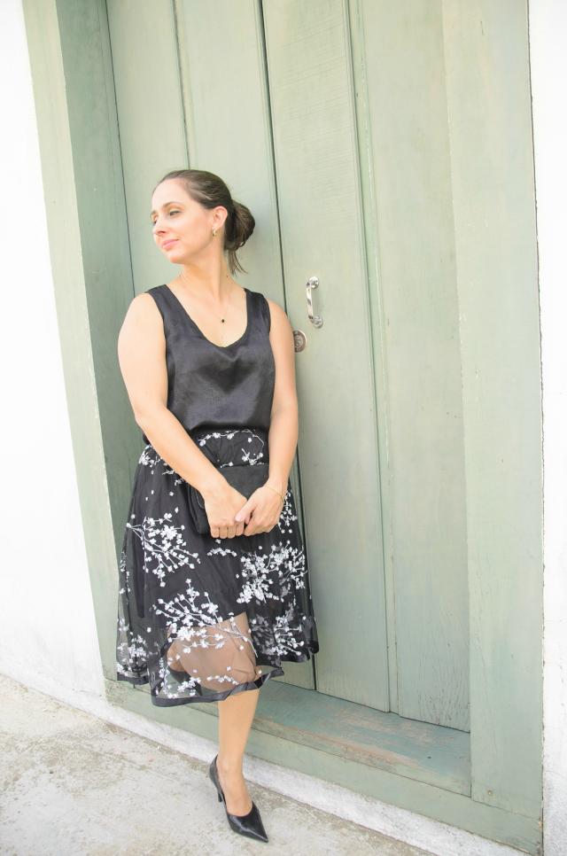 Saia com sobreposição transparente, blusa preta e scarpin de vinil preto