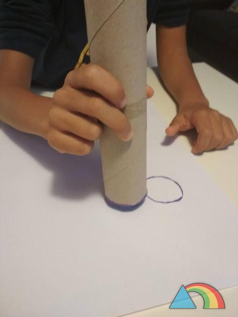 Niño estampando con un rollo de cartón círculos de color lila para dibujar un racimo de uvas