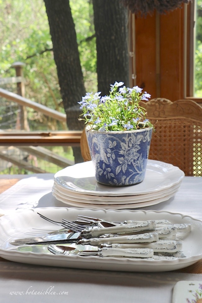 French Country Everyday Table Setting with dishes and scroll flatware left out between use