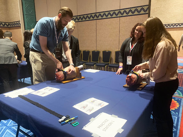 USU's Dr. Craig Goolsby demonstrates how to use a tourniquet for high school students at a conference.