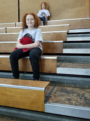 Two children sitting on Manchester Giants Basketball court seating wooden benches