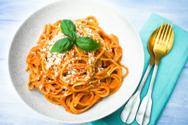 Red Pepper and olive spaghetti in white bowl, overhead shot