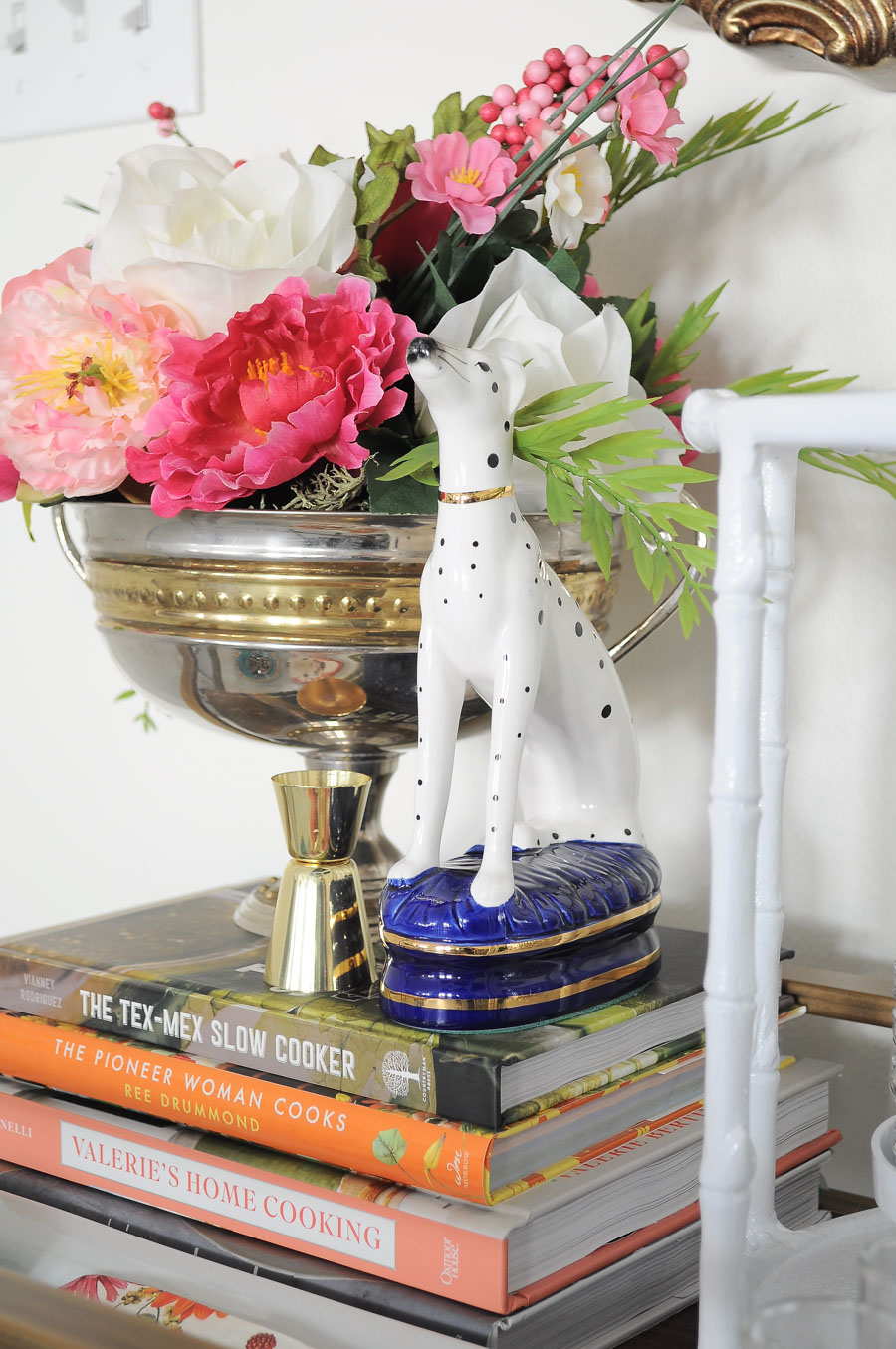 A faux floral arrangement looks chic next to a Fitz & Floyd dalmatian bookend on a bar cart.