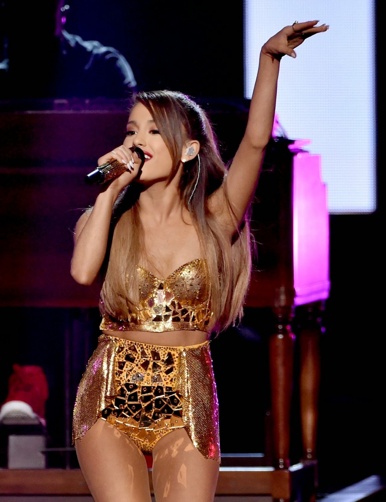 Ariana Grande performs at the 2014 American Music Awards in a gold cropped top and mini skirt