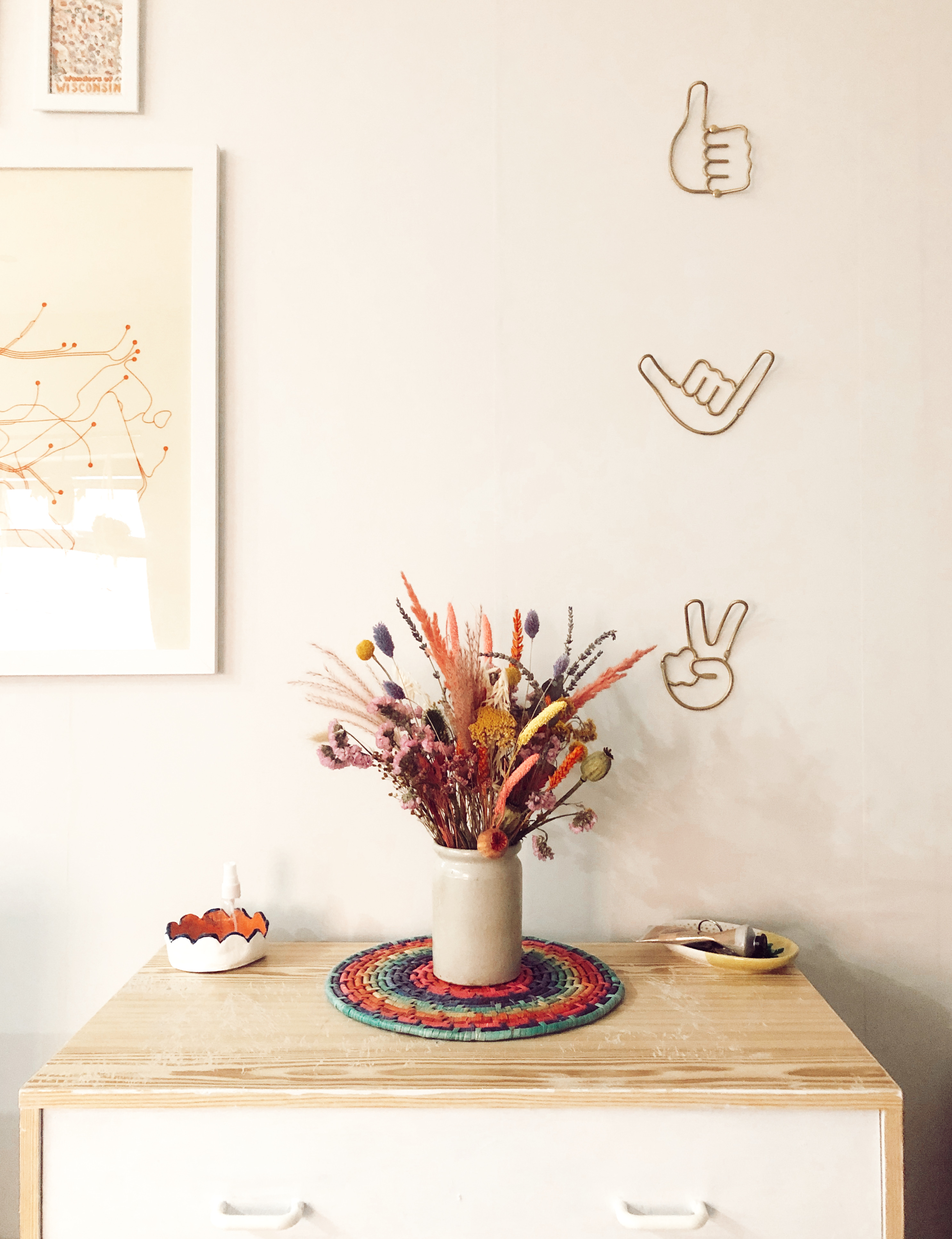 bouquet of colourful dried flowers on top of light wooden cabinet against white wall with prints and gold hand shaped hooks