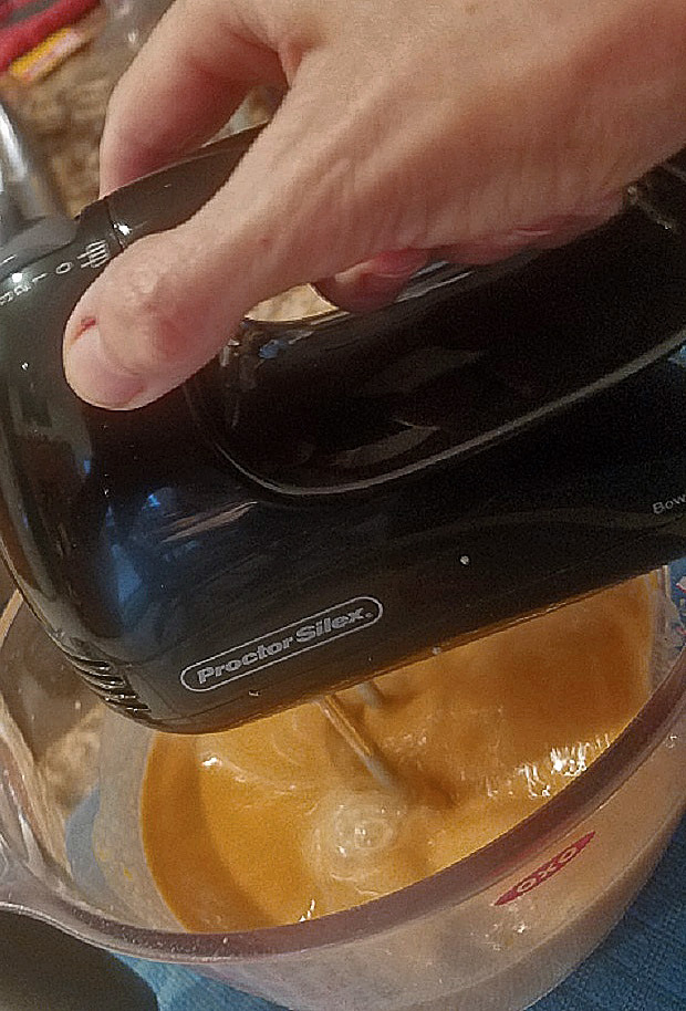 this is pumpkin cake batter in a plastic bowl with a hand mixer from Proctor Silex